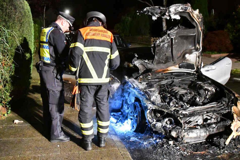 Polizei und Feuerwehr untersuchen ein ausgebranntes Auto.