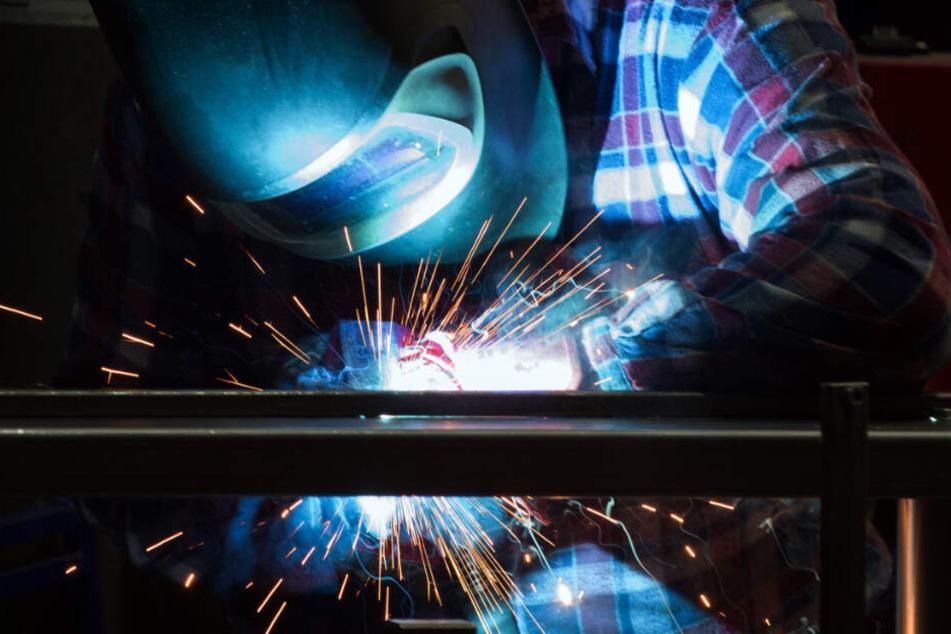 Ein Arbeiter schweißt Maschinenteile zusammen.