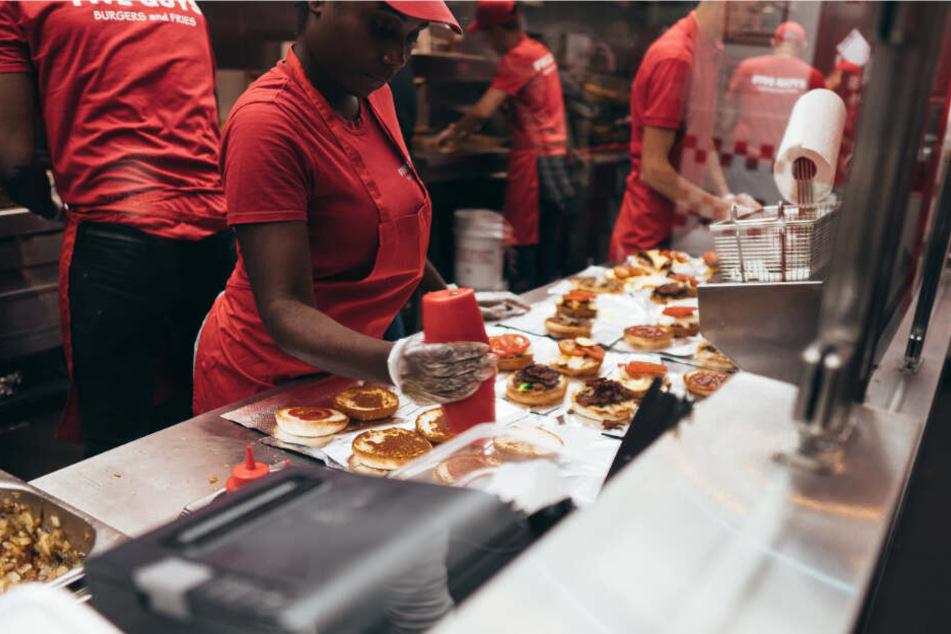 Five Guys Mitarbeiter bereiten Burger zu.