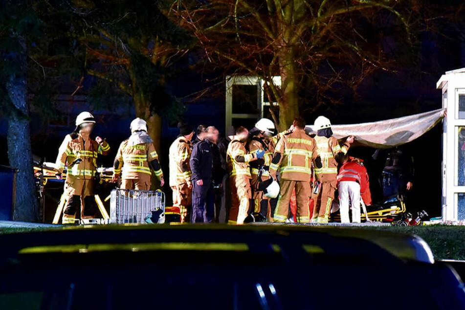 Feuerwehrleute, Sanitäter und Notärzte kümmern sich vor dem Haus um die Verletzten.