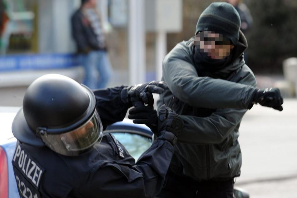 Ein Demonstrant schlägt zu: Gewalt gegen Polizisten umfasst alle Formen von verbaler Gewalt bis hin zu Körperverletzung und Tötung.