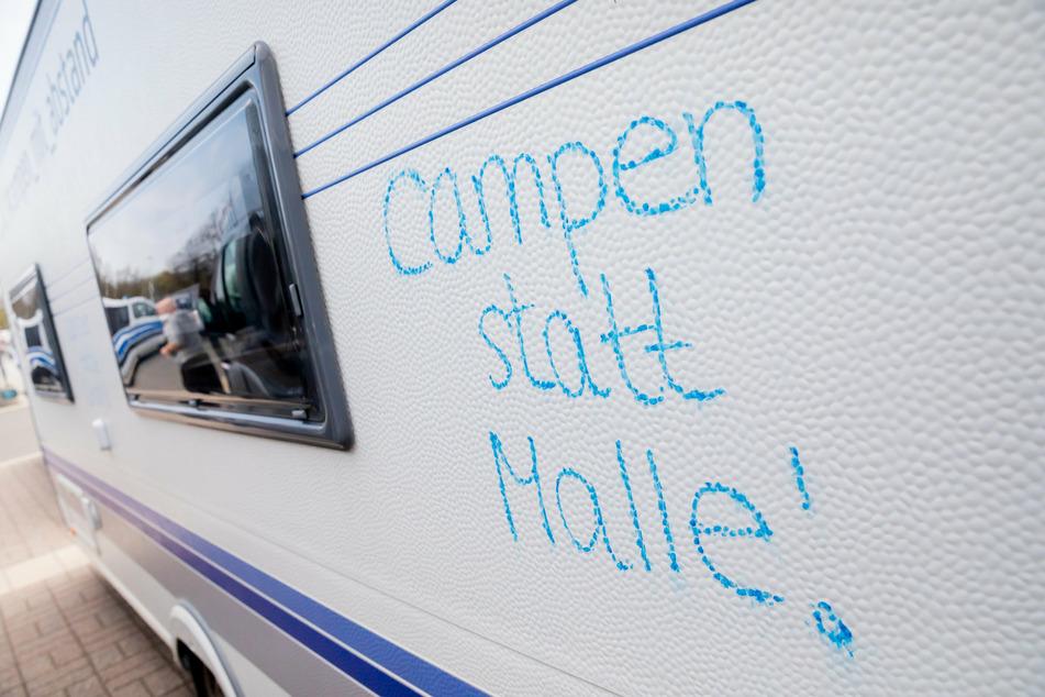 """""""Campen statt Malle!"""" steht vor dem Start eines Camper-Korsos der Camperinitiative """"Campen mit Abstand"""" am Olympiastadion auf einem Wohnwagen."""