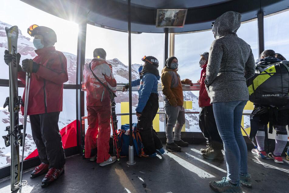 """Skifahrer mit Mund-Nasen-Schutz sind mit der Luftseilbahn """"Rotair"""" auf den Titlis unterwegs."""