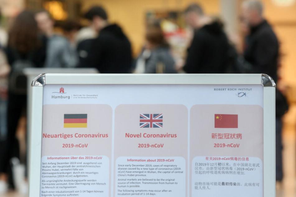 Ein Aufsteller am Hamburger Flughafen informiert in drei Sprachen über das Coronavirus.