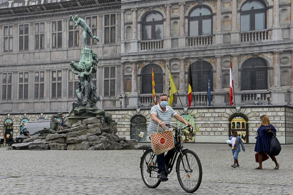 """Ein Mann fährt auf dem Fahrrad über den """"Grote Markt"""" der belgischen Stadt Antwerpen."""