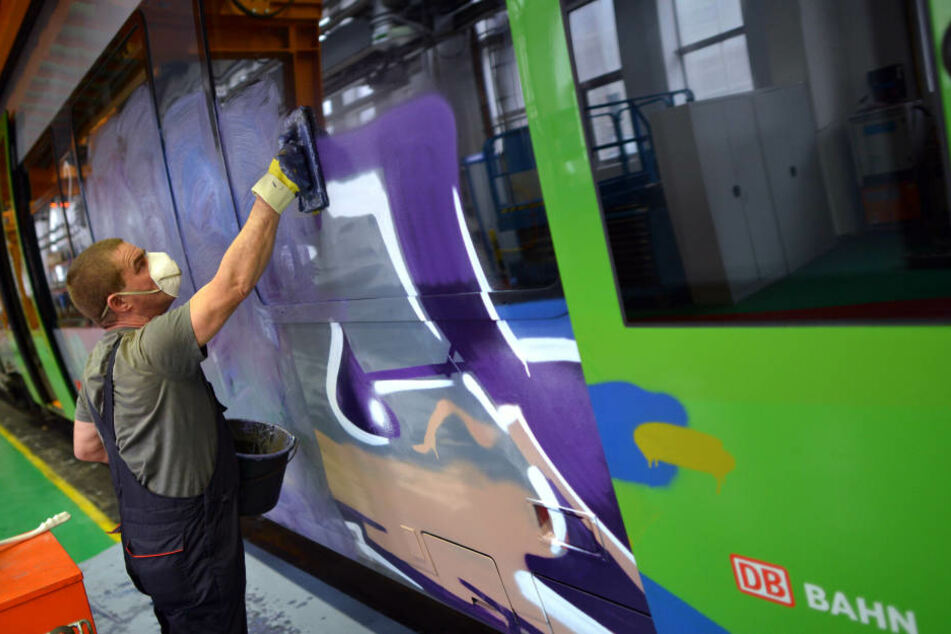 Ein Bahn-Mitarbeiter entfernt Farbe von einer S-Bahn nach einer Sprayer-Attacke. Bei einer weiteren Tat wurden nun in Leipzig sechs Männer festgenommen. (Symbolbild)