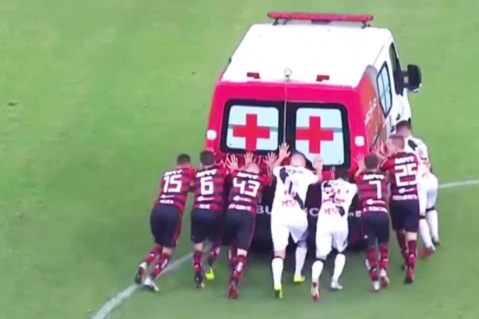 Verfeindete Fußballspieler schieben Rettungswagen vom Platz