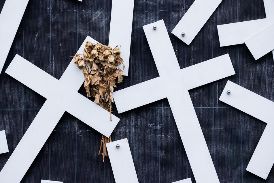 Vertrocknete Rosen stecken an einem Kreuz am Denkmal für die Opfer der Loveparade-Katastrophe.