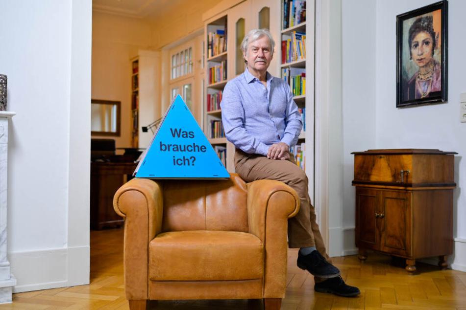 """Ernst Fritz-Schubert sitzt auf einer Sessellehne, neben ihm steht ein Dreieck mit der Aufschrift """"Was brauche ich"""""""