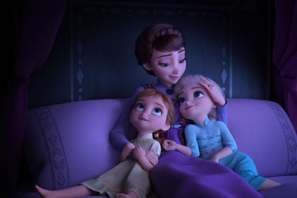 Königin Iduna (M.) erzählt ihren Töchtern Elsa (r.) und Anna eine Geschichte und singt für sie.