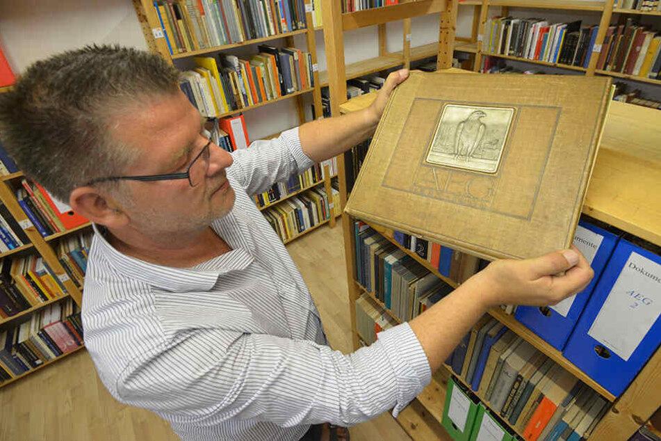 Ingo Pötschke (53) hält eine Festschrift der Firma SIEMENS aus dem Jahr 1908 in den Händen.