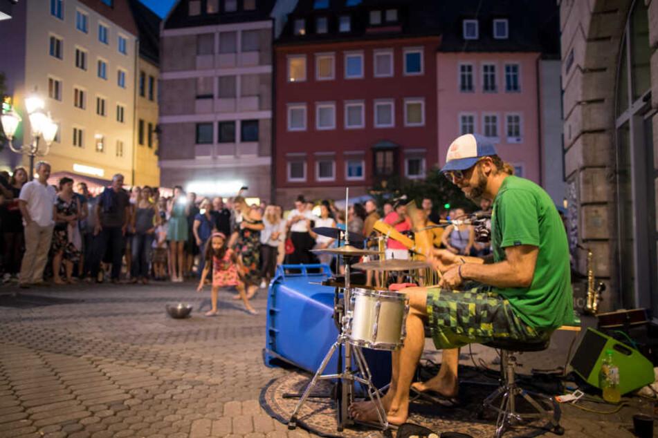 Ein Straßenmusiker spielt beim Nürnberger Bardentreffen auf einem Schlagzeug, das zum Teil aus einer Mülltonne besteht.