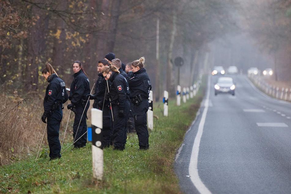 Polizisten suchten in einem Wald an einer Landstraße nach Spuren.