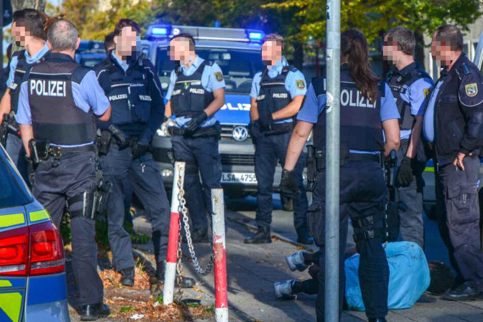 Mehrere Polizisten stehen neben dem blutend am Boden liegenden Chaoten. Er hatte zuvor Autos mit Glasflaschen beworfen und war in die Scherben gestürzt.