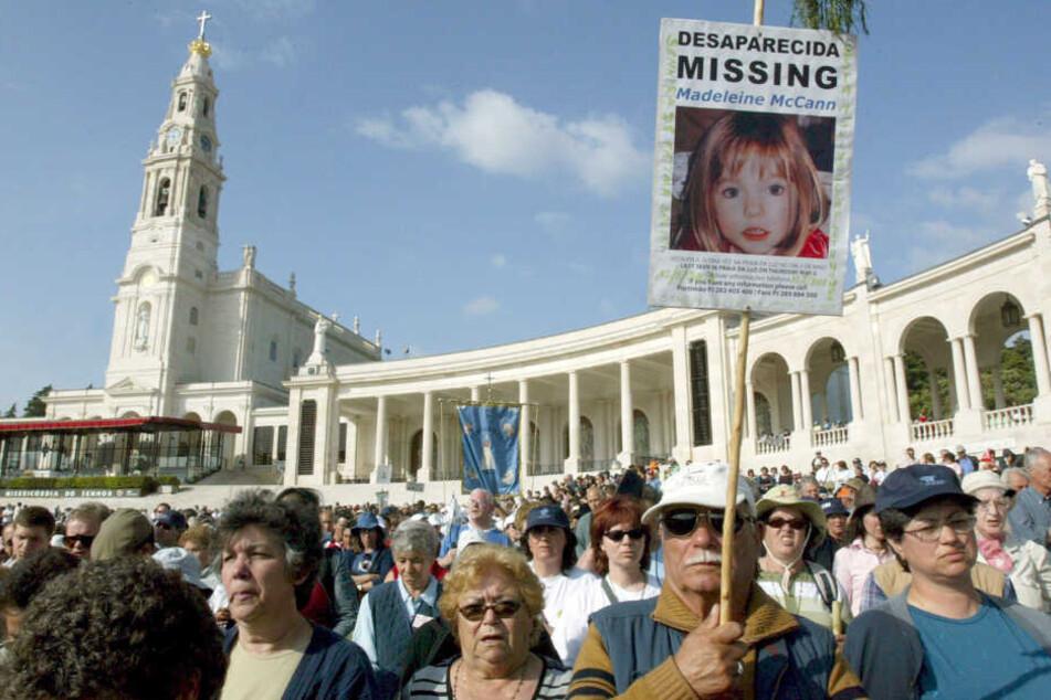 Im Wallfahrtsort Fatima halten Gläubige ein Plakat mit einem Foto von Maddie hoch. (Archivbild).