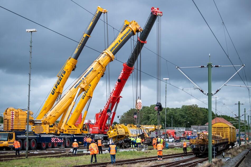Mit Autokränen wird daran gearbeitet, den mehr als 100 Tonnen schweren entgleisten Schienenbaukran wieder aufzurichten.