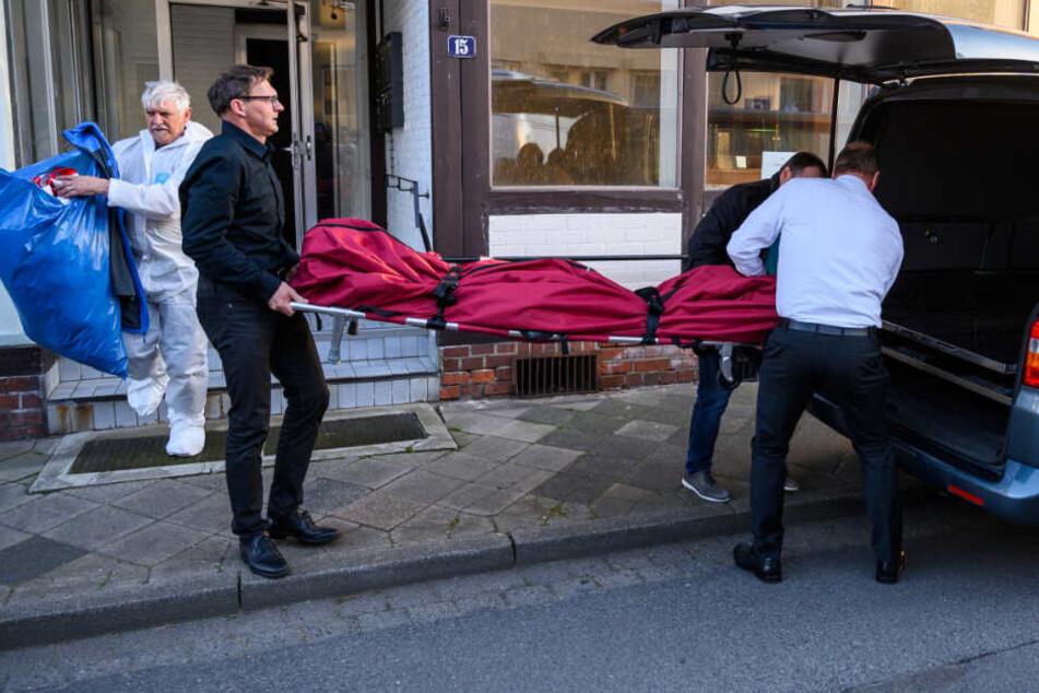 Bestatter schieben einen Leichensack in einen Leichenwagen. Im Zusammenhang mit dem Passauer Armbrust-Fall haben Ermittler zwei Leichen in Niedersachsen gefunden.