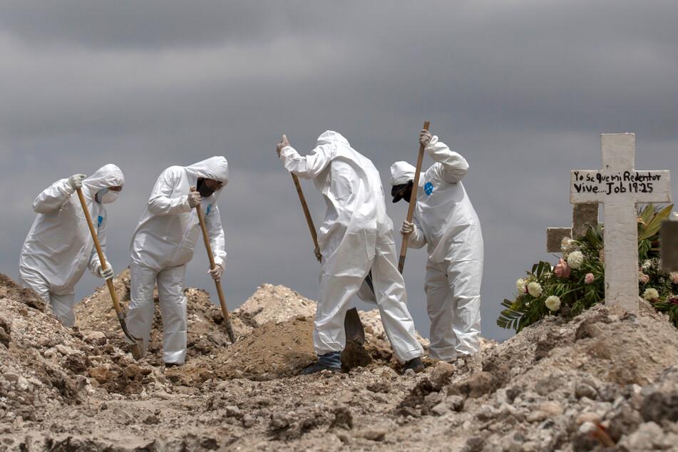 Mexiko, Tijuana: Arbeiter in Schutzanzüge schaufeln Erde bei einer Beerdigung im Rahmen der Covid-19-Pandemie. Im staatlichen Friedhof Nr. 13 werden Covid-19-Todesopfer unter Einhaltung besonderer Maßnahmen bestattet.