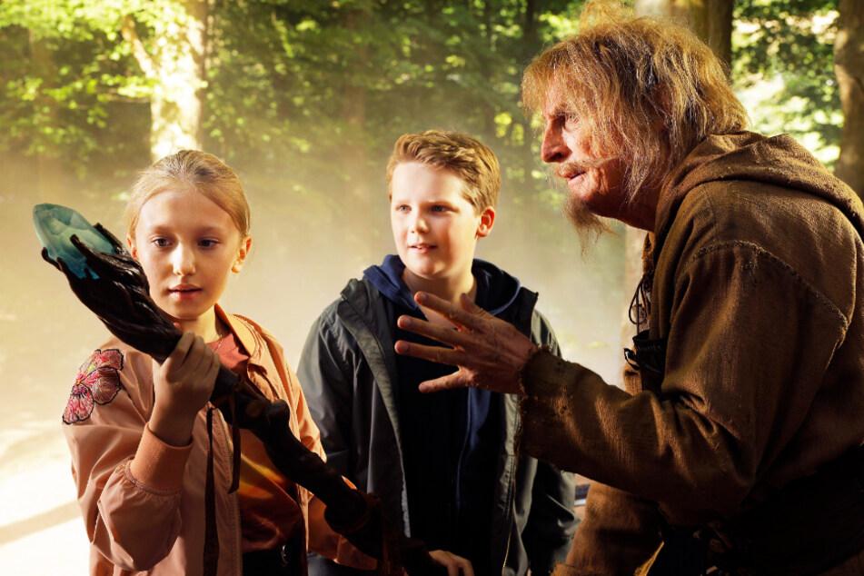 Catweazle (Otto Waalkes, r.) zeigt Lisa (l., Gloria Terzic) und Benny (Julius Weckauf), wie man mit einem Zauberstab richtig umgeht.