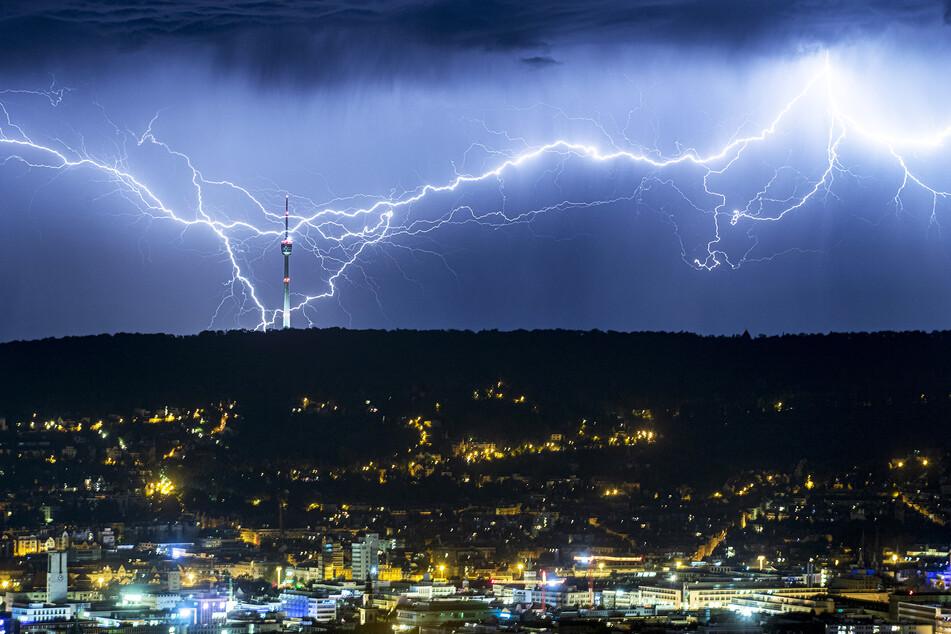 Blitze zucken des Nachts hinter dem beleuchteten Stuttgart am Horizont, und schlagen nahe des Fernsehturms ein.