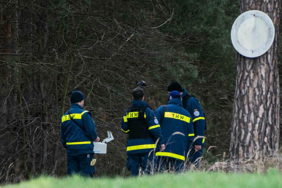 Mitglieder einer Spezialgruppe des Technischen Hilfswerks (THW) stehen mit einem Bodenradargerät in einem Wald bei Storkow.