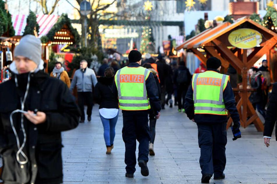 Zwei Polizisten laufen auf dem Weihnachtsmarkt am Breitscheidplatz Streife.