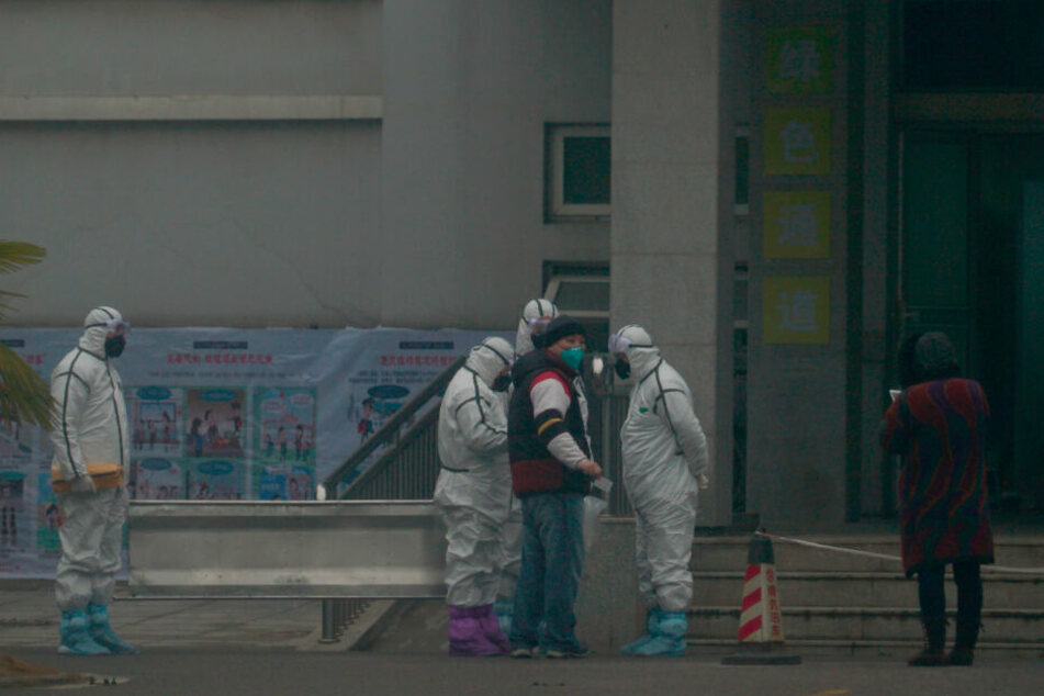 Mitarbeiter in Schutzanzügen stehen vor dem Wuhan Medical Treatment Center, in dem ein Patient mit Verdacht auf den neuartigen Corona-Virus behandelt wurde.