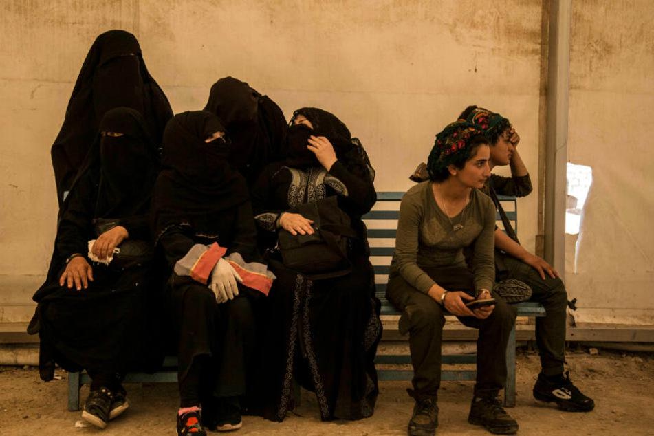 Frauen, die mit IS-Kämpfern verwandt sind, sitzen im Flüchtlingslager Al-Hol in Syrien.