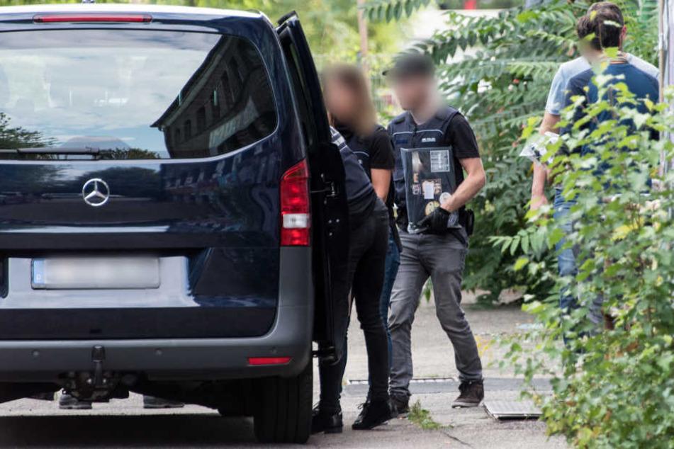 """Polizisten tragen vor dem autonomen Zentrum """"KTS"""" in Freiburg bei einer Durchsuchung Beweismaterial zu einem Polizeifahrzeug."""