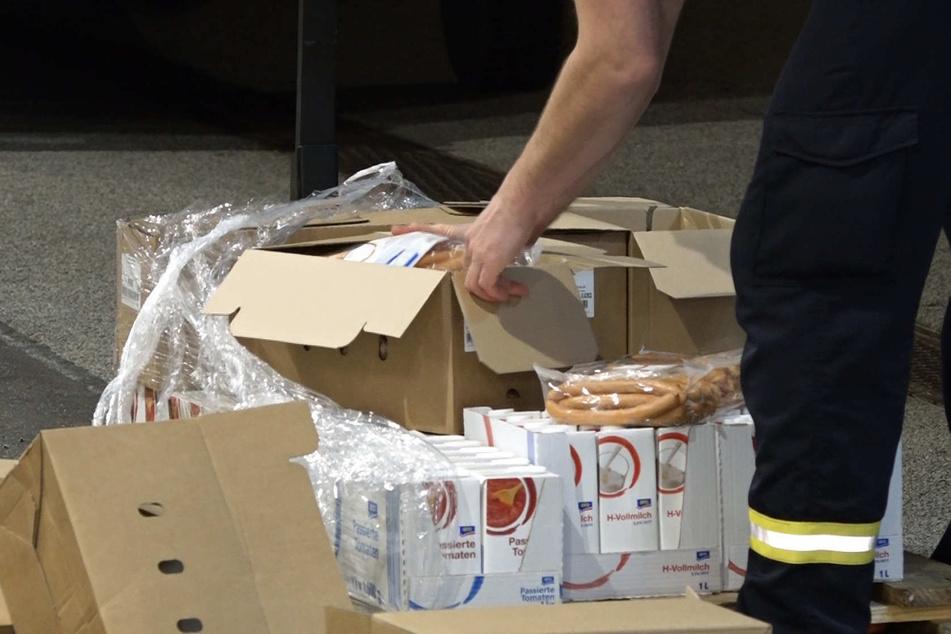 Einsatzkräfte versorgen die Wartenden mit Nahrung.