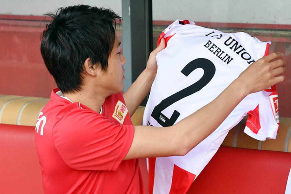 Uchida bestaunt sein neues rot-weißes Trikot mit der Rückennummer 2.