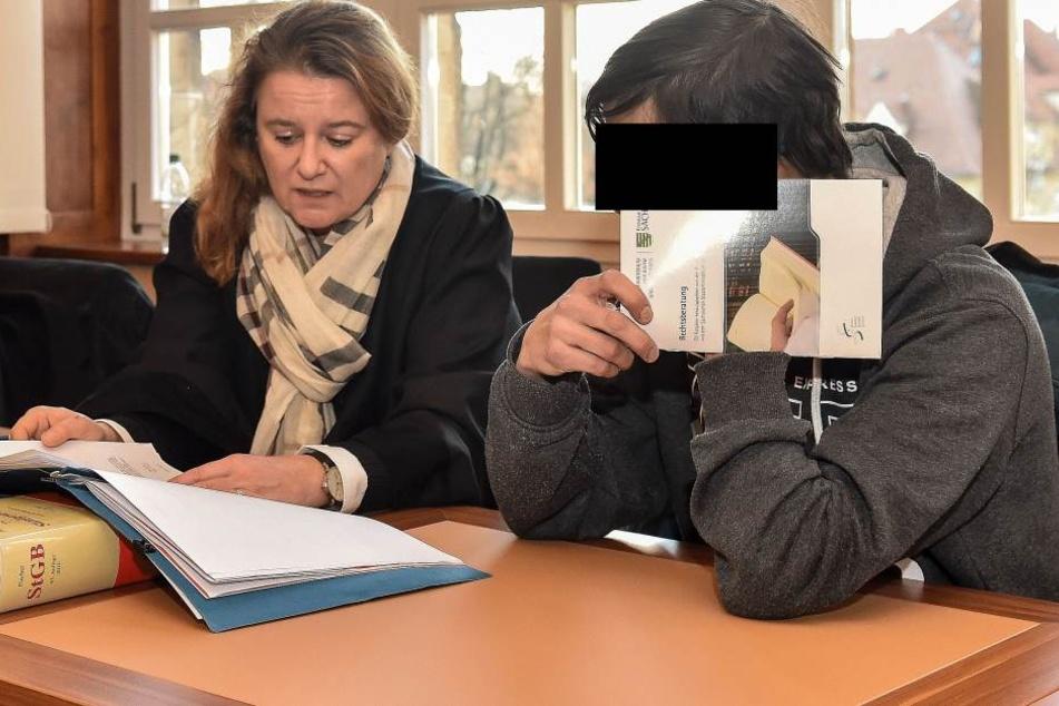 Philipp G. versteckt sein Gesicht hinter eine Justiz-Broschüre.
