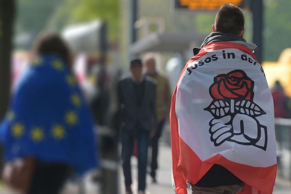 Ein Jungsozialist, kurz Juso, mit der Fahne der Nachwuchsorganisation bei einer Demo. Dass die Jusos nicht immer mit der SPD einer Meinung sind, wird bei der Linksextremismus-Debatte in Leipzig deutlich (Symbolbild).