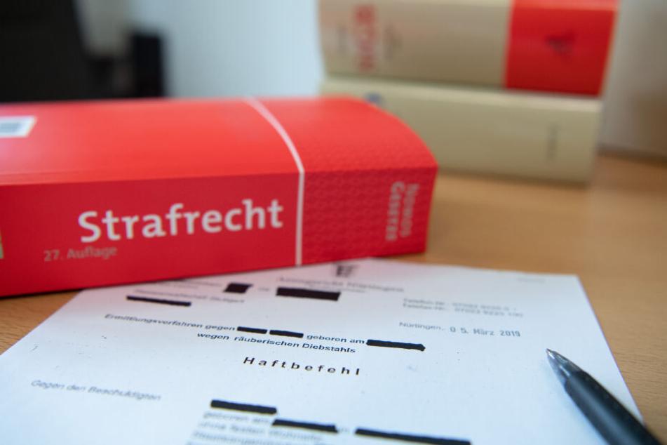 Eine Abschrift eines Haftbefehls liegt mit einem Strafrecht-Buch und einem Kugelschreiber auf dem Tisch.