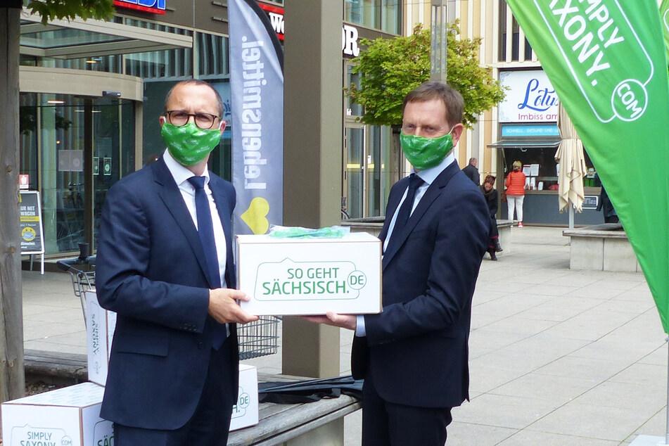 Sachsens Ministerpräsident Michael Kretschmer (r.) übergibt 1000 Mund-Nase-Masken an Toni Kunze, Geschäftsbereichsleiter Expansion der EDEKA Grundstücksgesellschaft Nordbayern-Sachsen-Thüringen mbH.