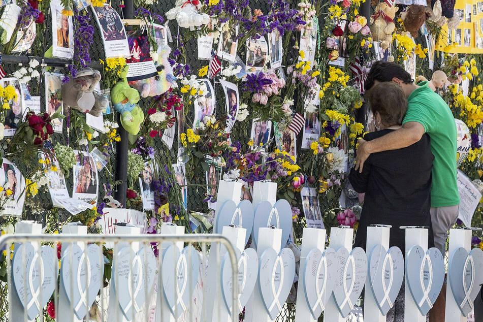 Menschen trauern an der Gedenkwand für die Opfer des Hauseinsturzes.