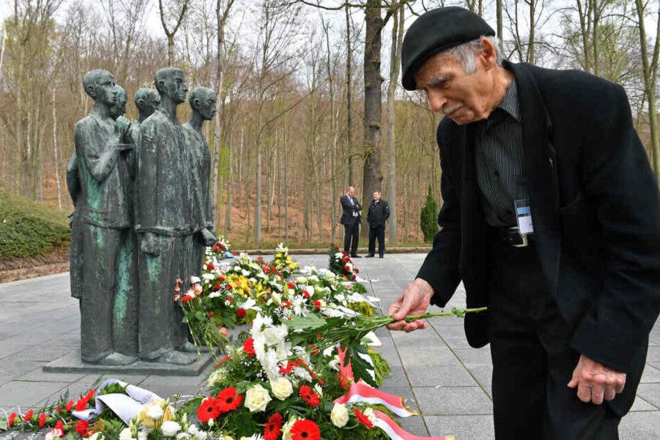 Vor dem Krematorium legt der früherer Häftling Pierre Berg aus Frankreich Blumen nieder.