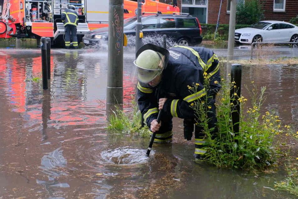 Ein Feuerwehrmann kämpft gegen die Wassermassen an einer Kreuzung.