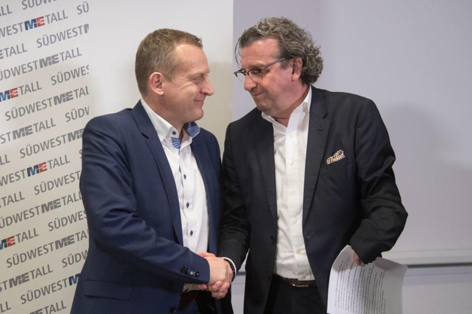Stefan Wolf (r.), der Vorsitzende der Arbeitgebervereinigung Südwestmetall und Roman Zitzelsberger, der Bezirksleiter der IG Metall Baden-Württemberg, geben sich in der Liederhalle nach einer Pressekonferenz zum Abschluss der Tarifverhandlungen die Hand.