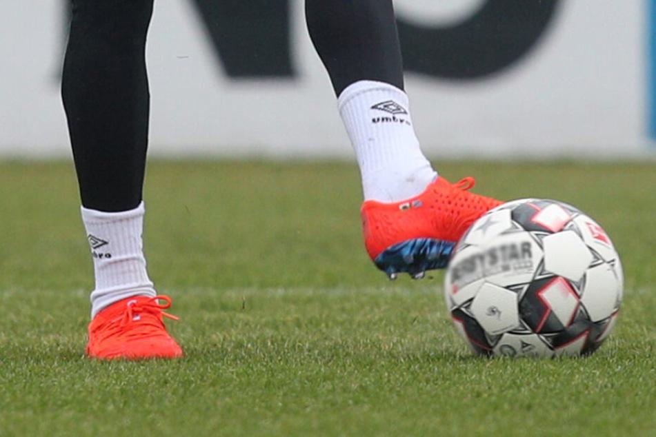 """Ein Fußballspieler kickt das """"Leder"""" (Symbolbild)."""