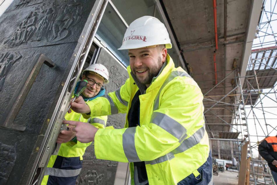 Oliver Domke (30, r.) und Christian Ullmann (48) von der Firma Fuchs+Girke  Bau setzten am Dienstag die erste restaurierte Tür ein.