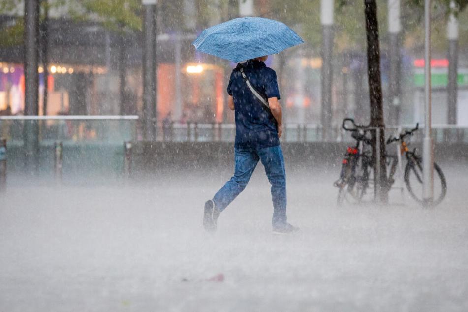 Ein Fußgänger spaziert mit einem Regenschirm durch den Regen.