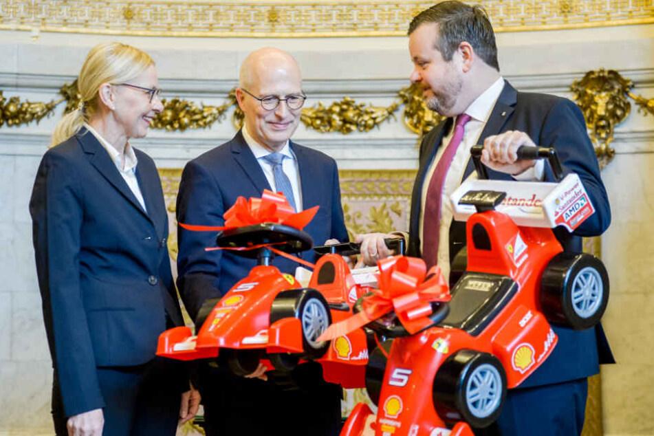 CDU-Fraktionschef André Trepoll (rechts) überreichte Bürgermeister Peter Tschentscher zwei ferrarirote Bobby-Cars für Hamburgs Zweite Bürgermeisterin, Katharina Fegebank.
