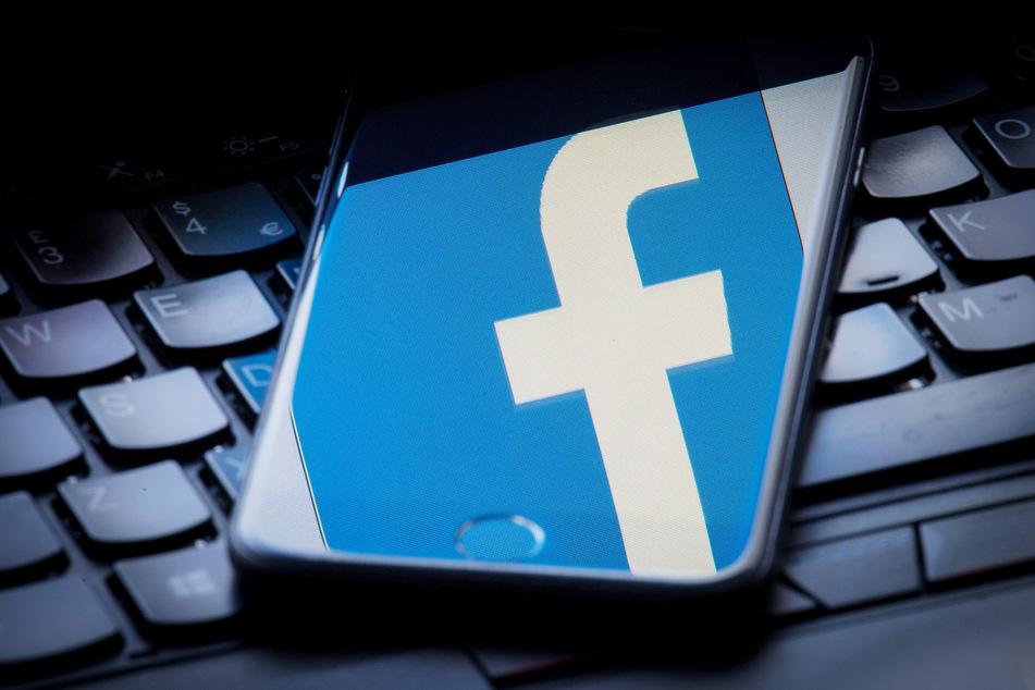 Das Facebook-Logo wird auf einem Smartphone gespiegelt, das auf einer Tastatur liegt.