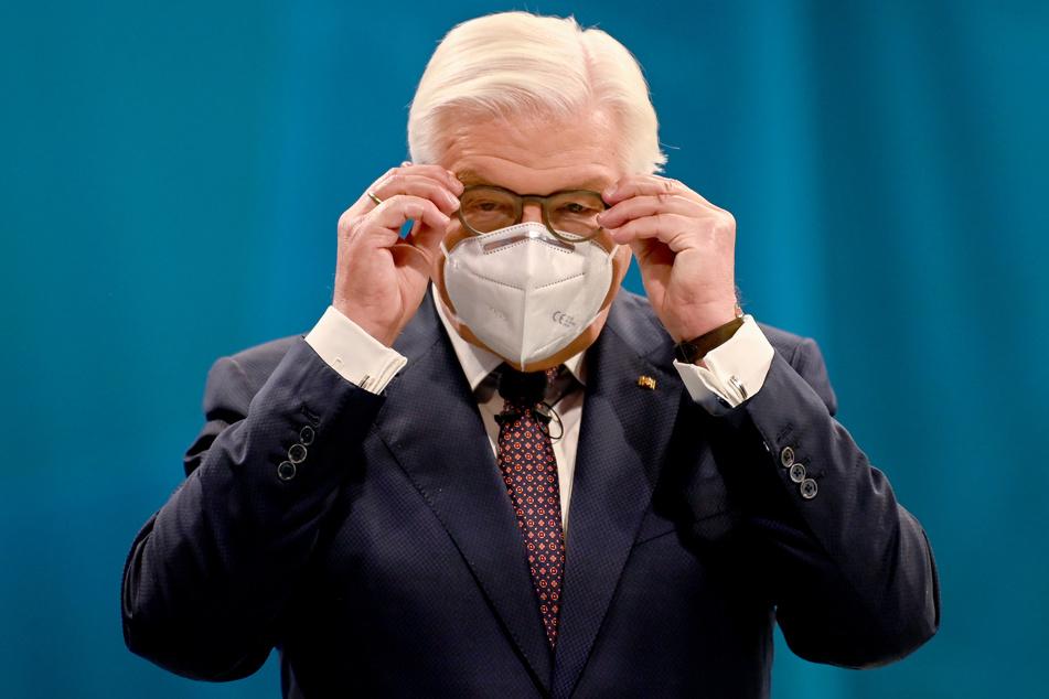 Bundespräsident Frank-Walter Steinmeier setzt sich einen Mund- Nasenschutz auf.