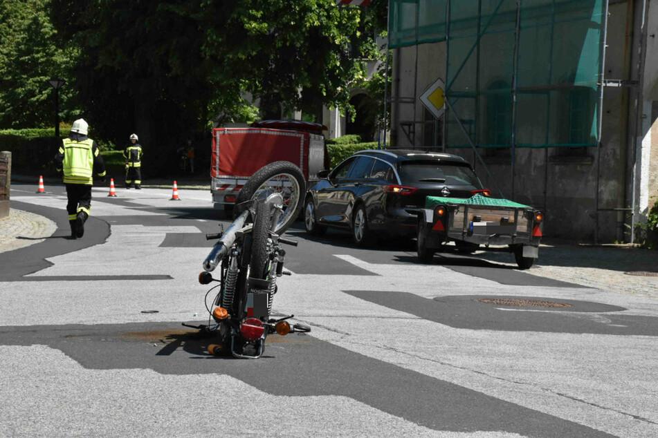 Das Moped fuhr gegen den grünen Fahrzeug-Anhänger (r.) und blieb auf dem Lenker liegen.