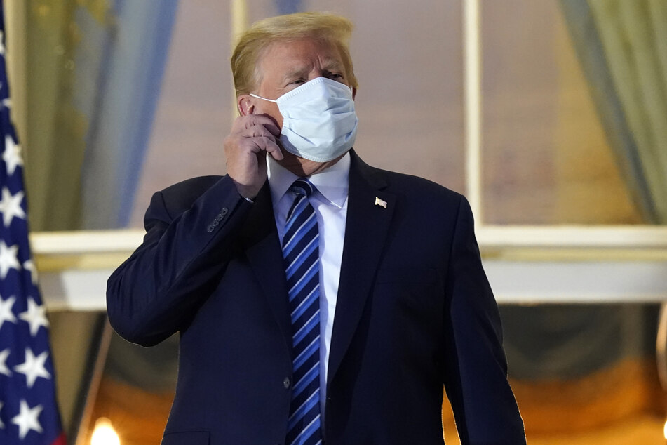 President Donald Trump taking off his mask after returning to the White House, following his hospitalization for Covid-19.