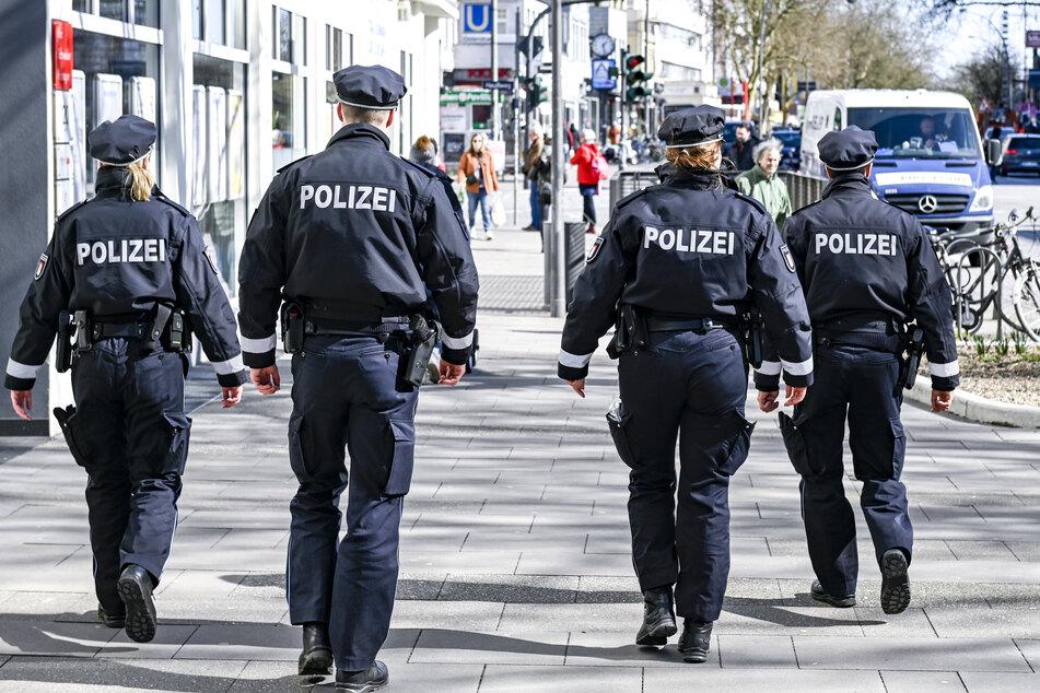 Polizisten patrouillieren vor dem Eingang zu einem Supermarkt auf einer Einkaufsstraße in Hamburg.
