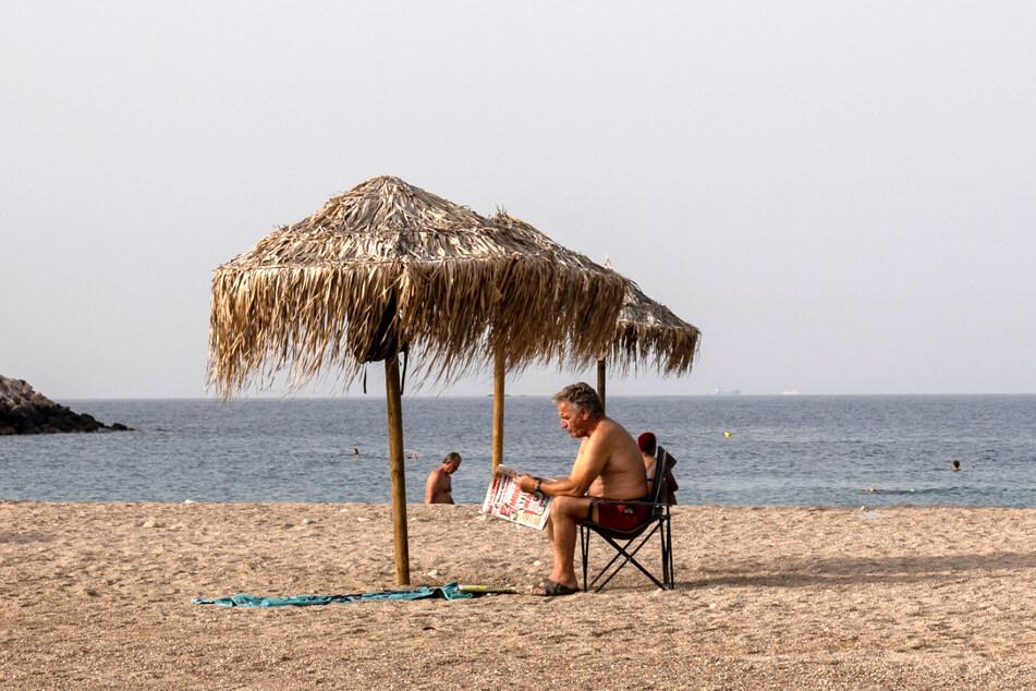 Schwitzen im warmen Griechenland: Ein Mann liest eine Zeitung an einem Strand in Glyfada (Athen).