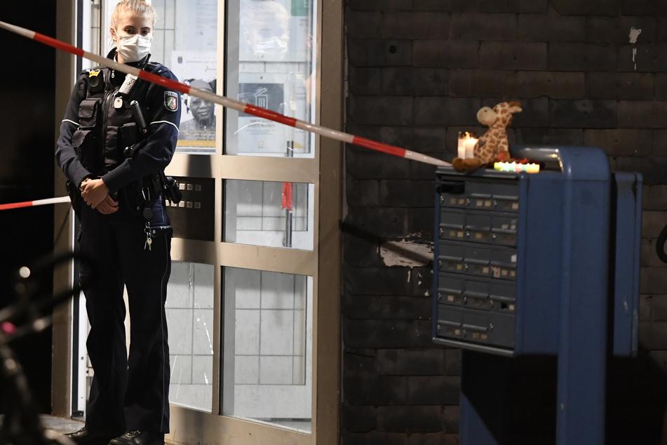 Eine Polizistin steht in Solingen vor dem Hauseingang, hinter dem eine Mutter (27) fünf ihrer Kinder getötet haben soll.